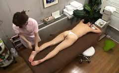 Petite girl lies on the massage table and is made to reach