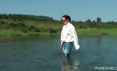 Clothed slut sensually touching wet body in the lake