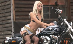 Hot blonde bimbo poses on a motorbike